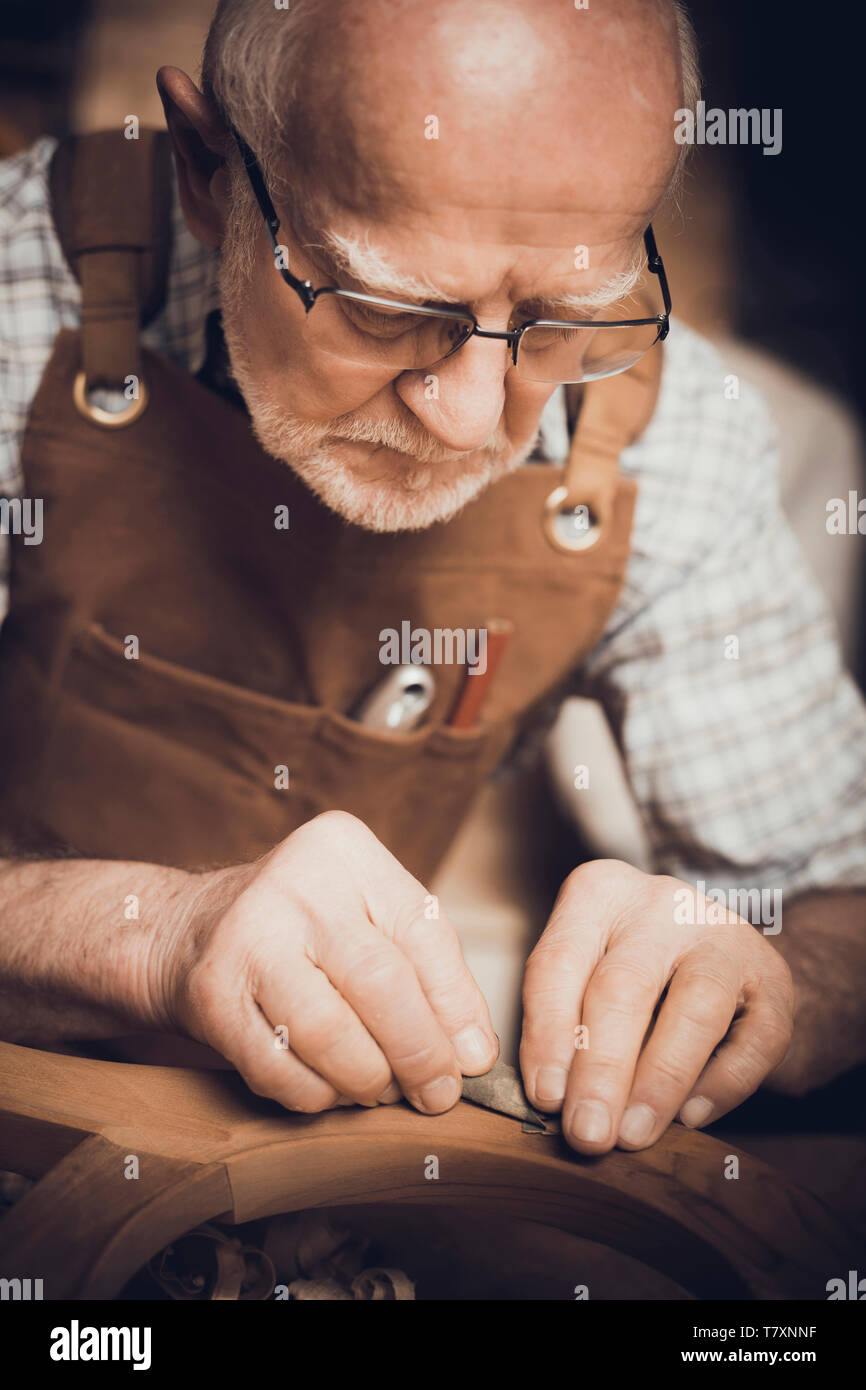 Senior carpenter who was busy polishing a wooden object inside his workshop. - Stock Image