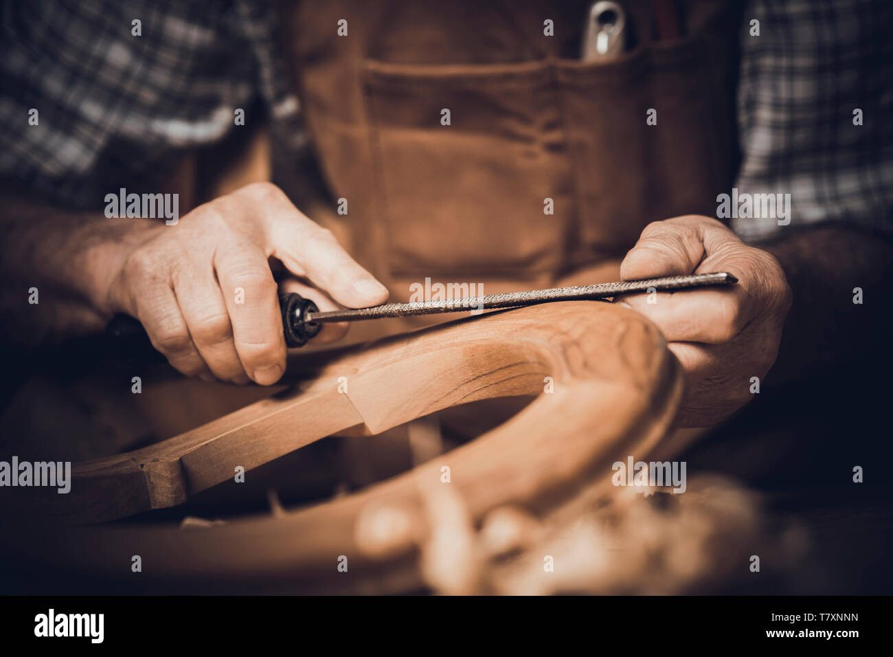Detail of a carpenter using a wooden rasp on a chair. inside his workshop. - Stock Image
