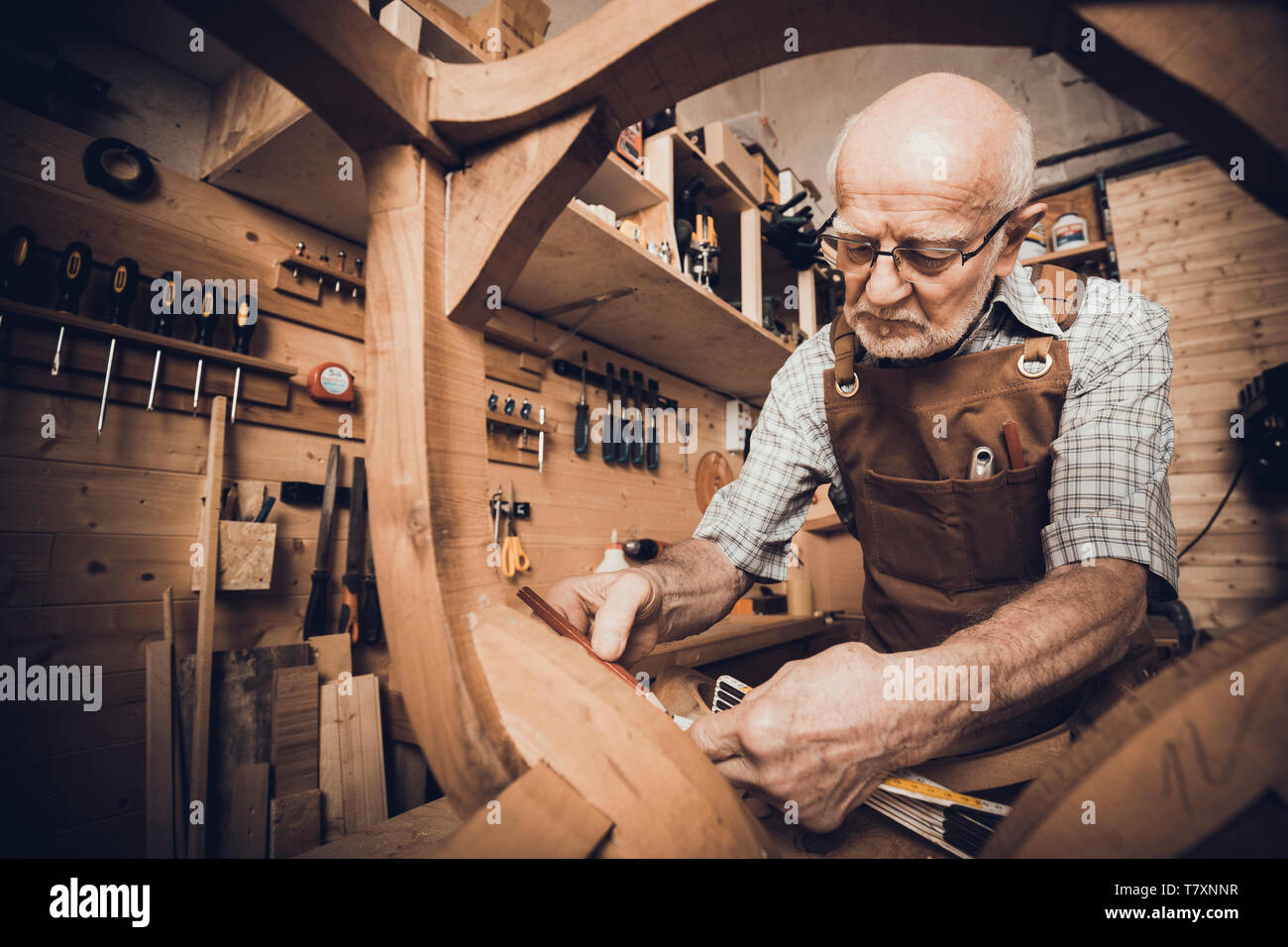 An old carpenter takes measurements at a chair to be restored, a workshop with tools in the background. - Stock Image