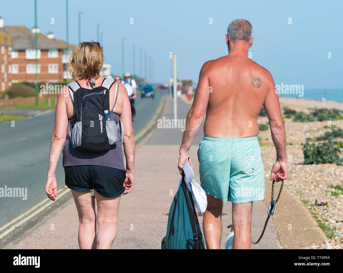 Middle aged people, possibly a couple, shirtless and walking along a pavement by a main seafront road on a hot day in Spring in England, UK. - Stock Image