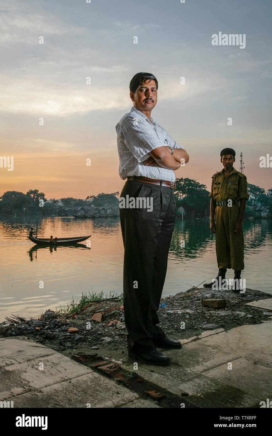 One meter of se level rise will put twenty percent of our country under water, says climate scientist Mozaharul Alam. Here he is next to the all encompassing water in the capital city Dhaka. Bangladesh is prone to a double whammy of flooding and drought caused by the melting glaciers of Himalaya. - Stock Image