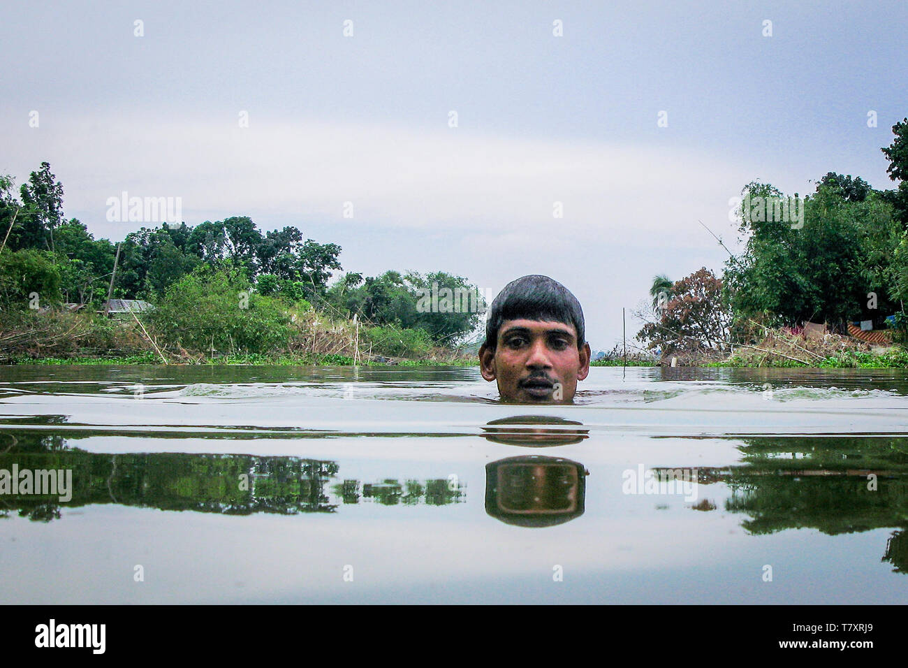 Mohammad Khokon swims in the Jamuna River where his house used to be. A flash flood washed it into the Jamuna River in Sirajganj, Bangladesh in 2007. Global warming cause the monsoon rain and floods to start earlier. Global warming also accellerate the melting of the ice and snow in the Himalayas, which feeds into the already saturated rivers that make the Ganges Delta. The result is devastating to people who live in the densely populated delta area. While the Himalayas and flooding wreak havoc from the north, rising sea levels cause salt water intrusion in the low-lying agricultural zones alo - Stock Image