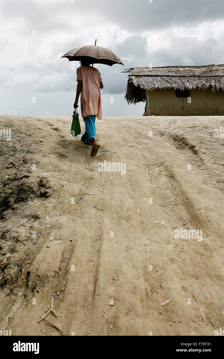 A man with an umbrella walks up the steep edge of a flood levee built to shield the Burigoalini against flooding and storm surge. Bangladesh is prone to a double whammy of flooding and drought caused by the melting glaciers of Himalaya. - Stock Image