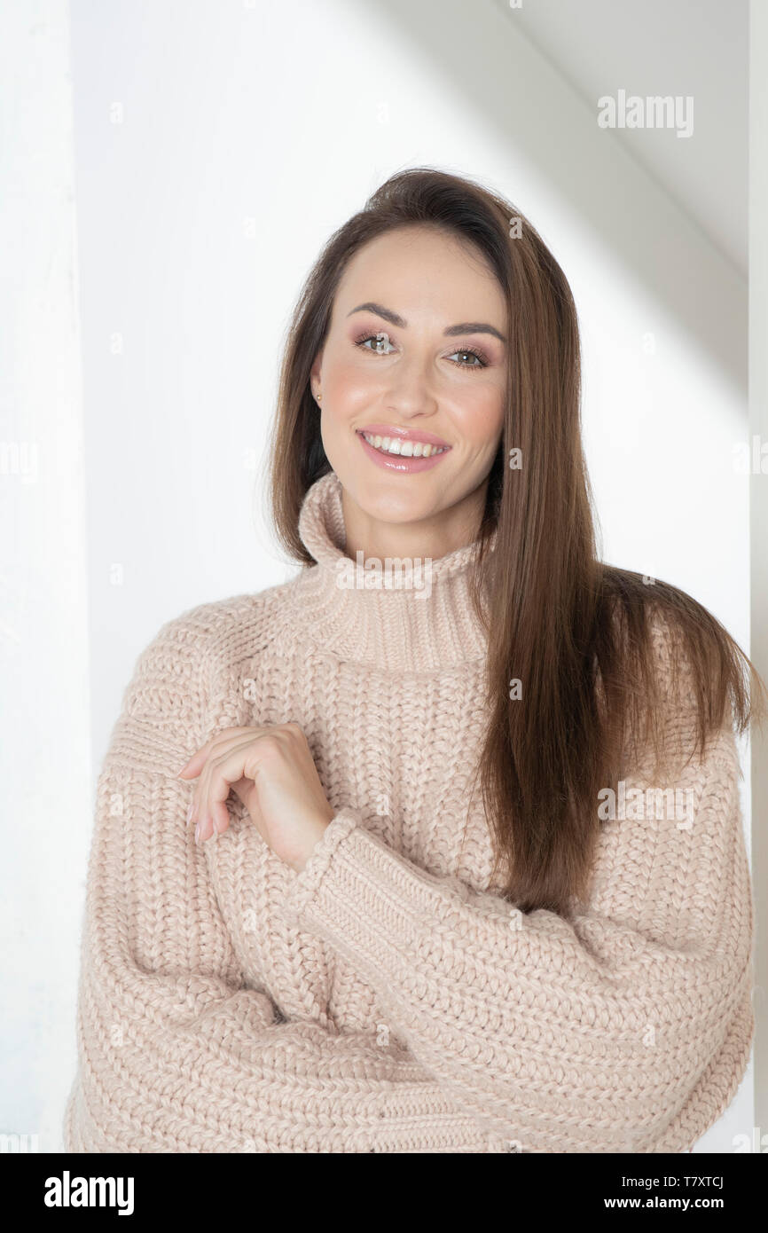 Smiling woman in beige sweater Stock Photo