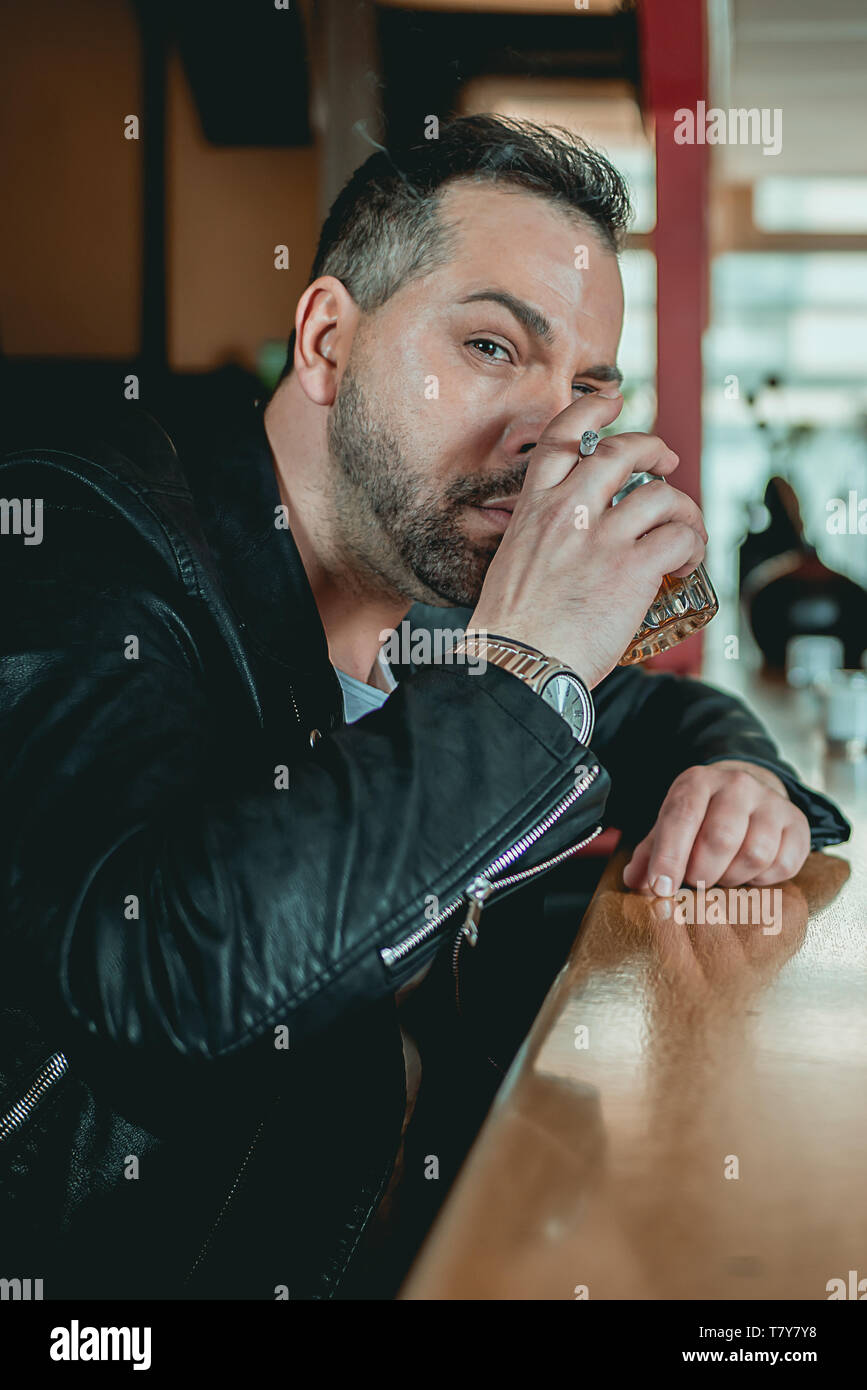 A Man in a bar at the counter looks up at the camera with raised eyebrow and whiskey in his hand - Stock Image