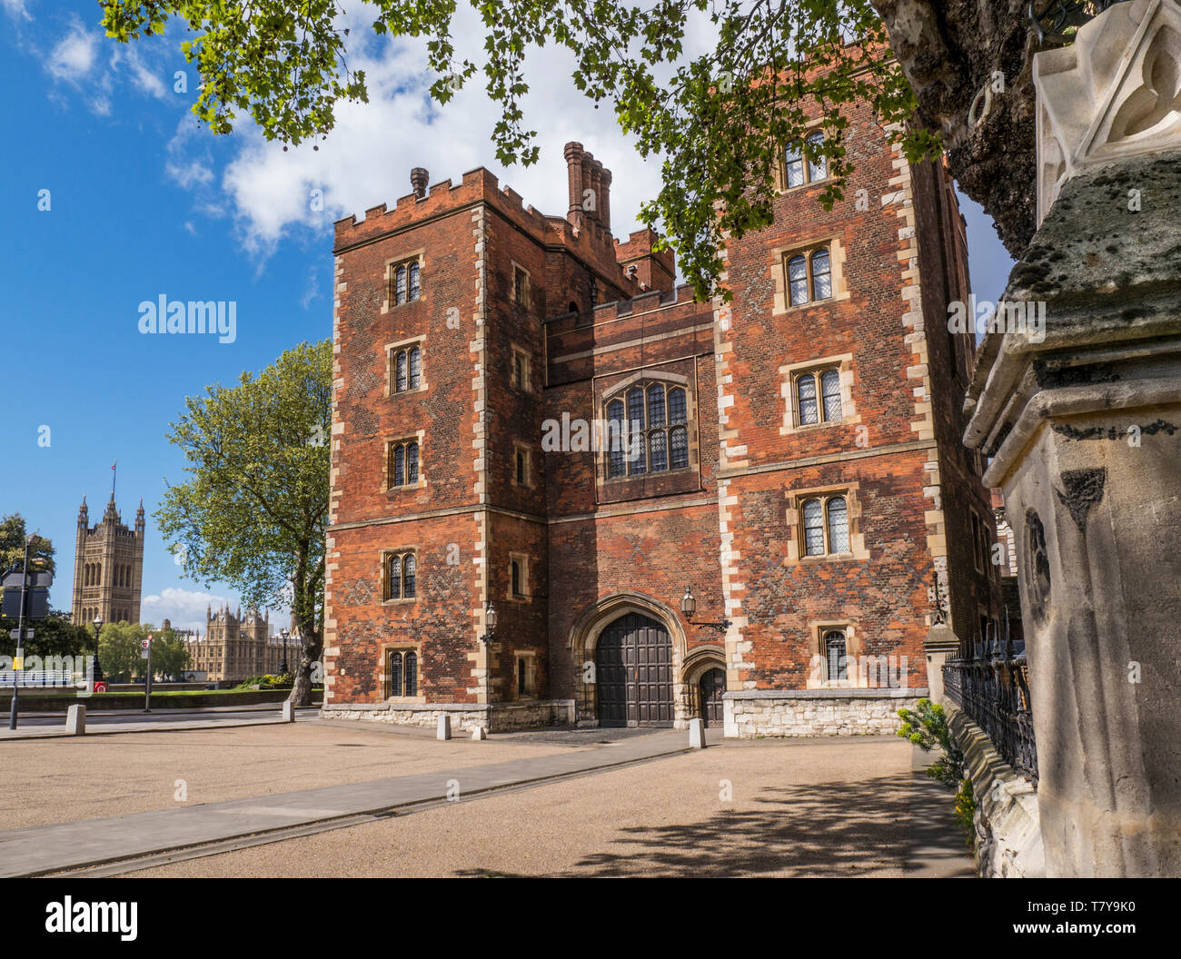 Lambeth Palace London. Morton's Tower with Houses of Parliament behind. Red brick Tudor gatehouse forming the entrance to Lambeth Palace London UK - Stock Image