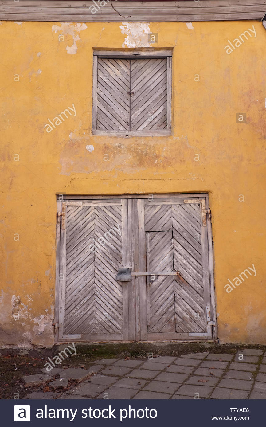 Wall Of Old Medieval Building With Yellow Flaking Walls Wooden Gate