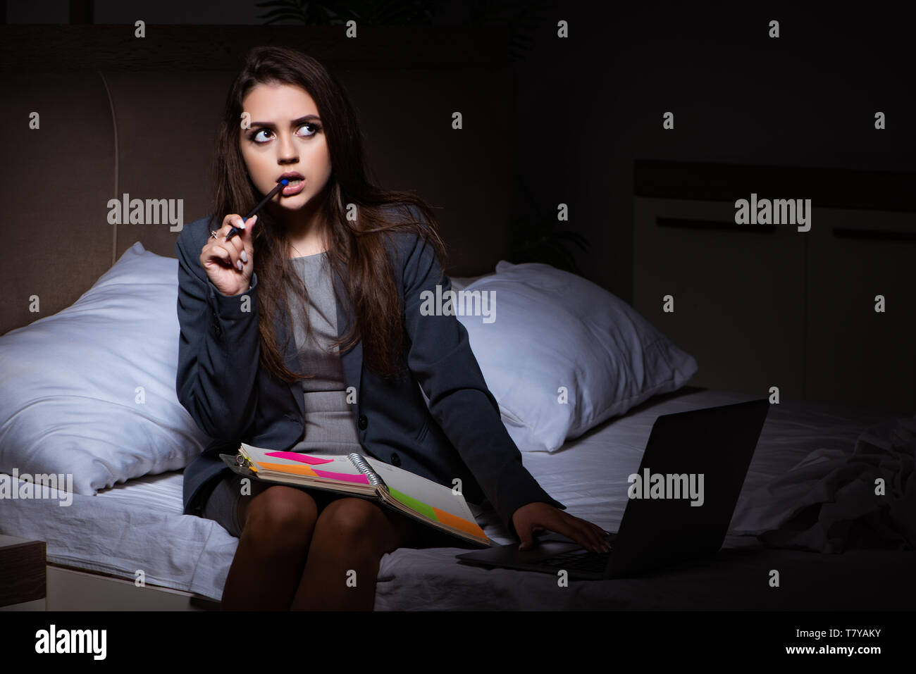 Tired businesswoman working overtime at home at night Stock Photo