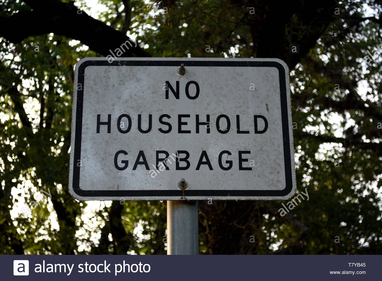 No Household Garbage. No Household Garbage Sign. Sign No Household Garbage. Household Garbage. No dumping household garbage. Sign with tree in Texas. - Stock Image