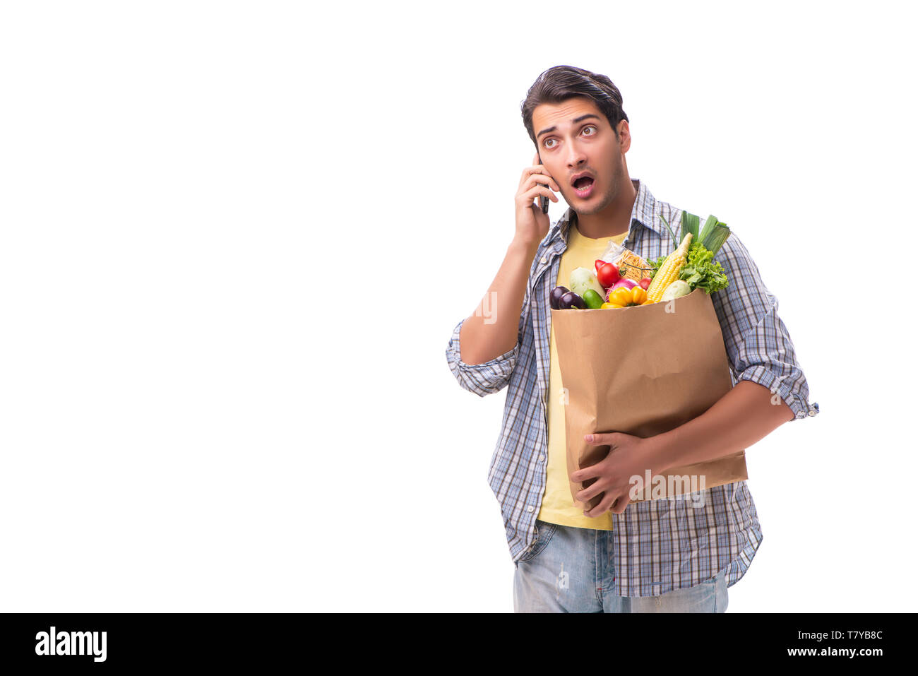 Young man with his grocery shopping on white - Stock Image