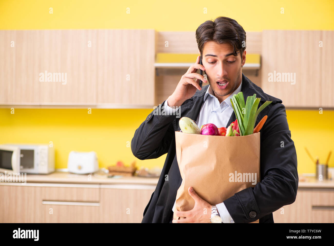 Young handsome man with vegetables in kitchen - Stock Image