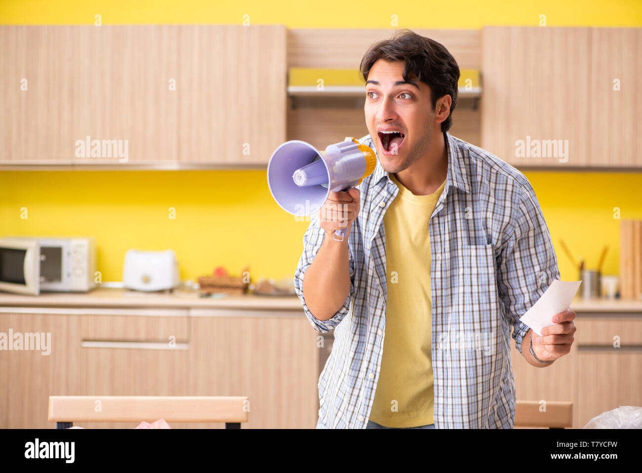 Young man calculating expences for vegetables in kitchen - Stock Image