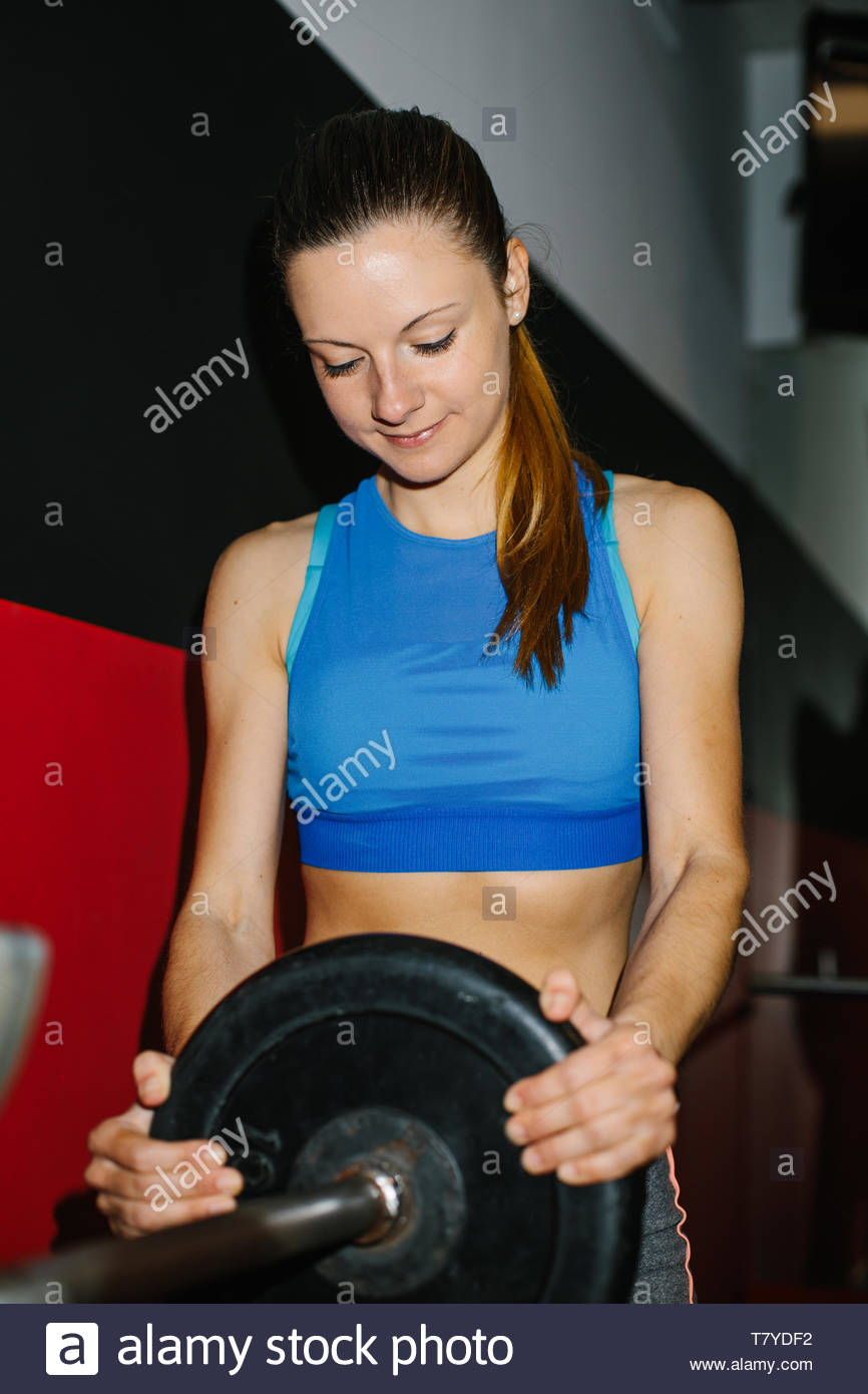 Young fitness woman working out in the gym. - Stock Image