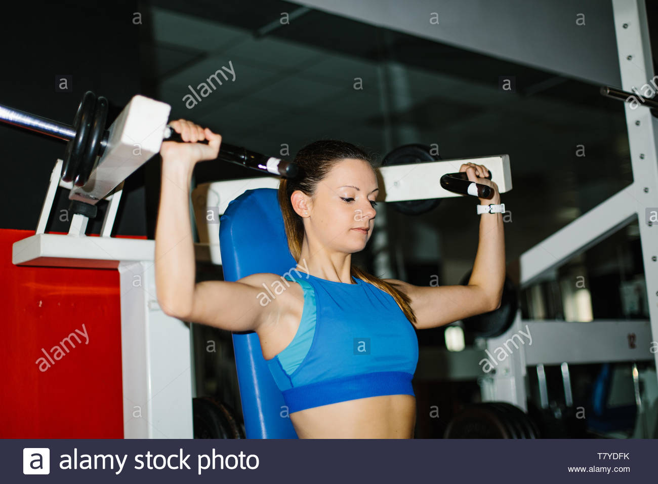 Young fitness woman working out in the gym. Shoulder press machine exercise. - Stock Image