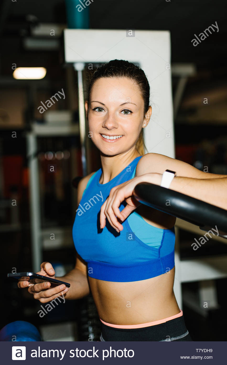 Young cheerful fitness woman working out in the gym. Fit girl taking a break for texting on smartphone. - Stock Image