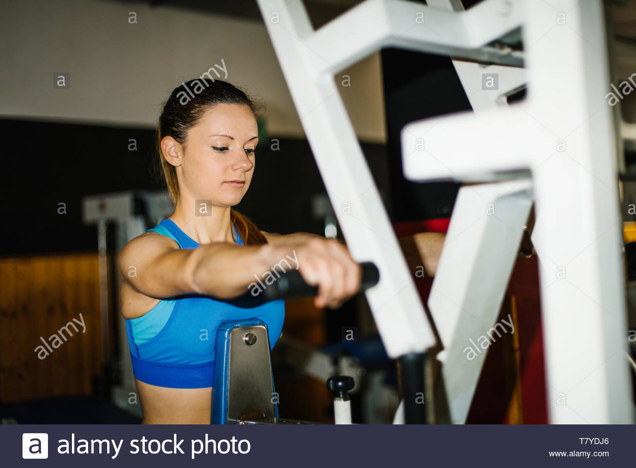 Young fitness woman working out in the gym. Back row exercising. - Stock Image