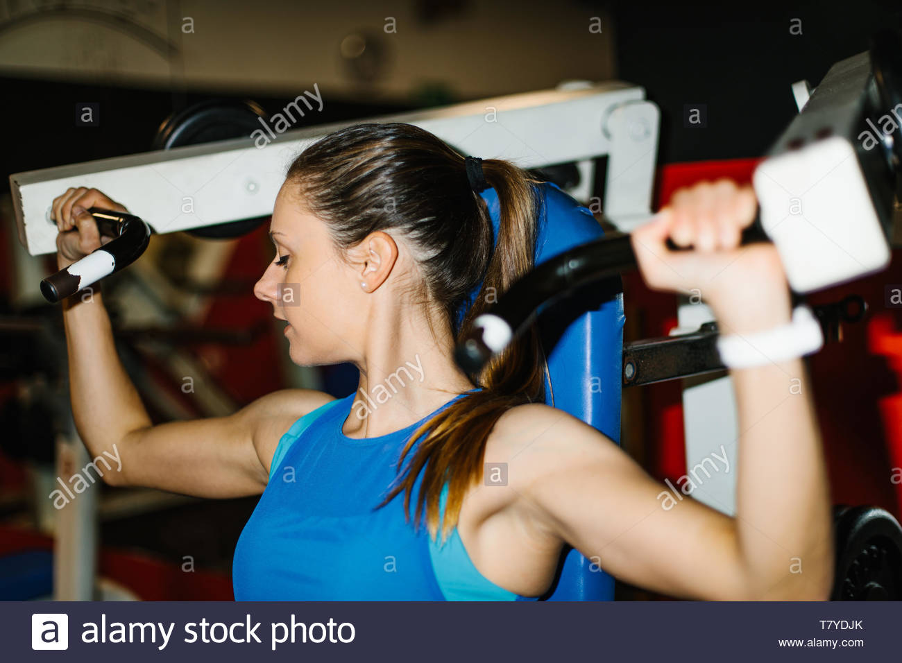 Young fitness woman working out in the gym. Shoulder machine exercise. - Stock Image