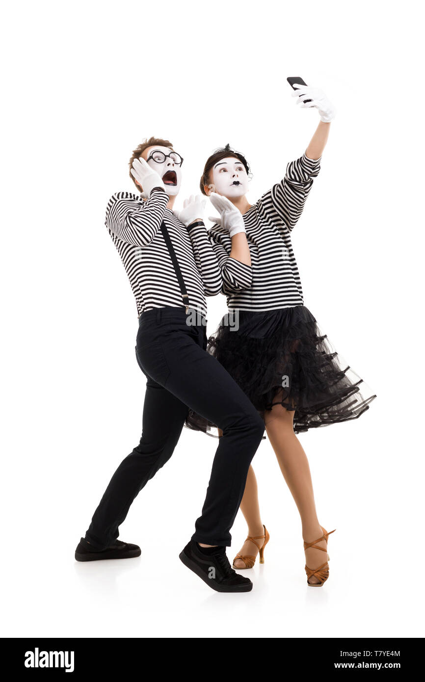 Smiling mimes in striped shirts. couple mimes making selfie on camera isolated on white background - Stock Image