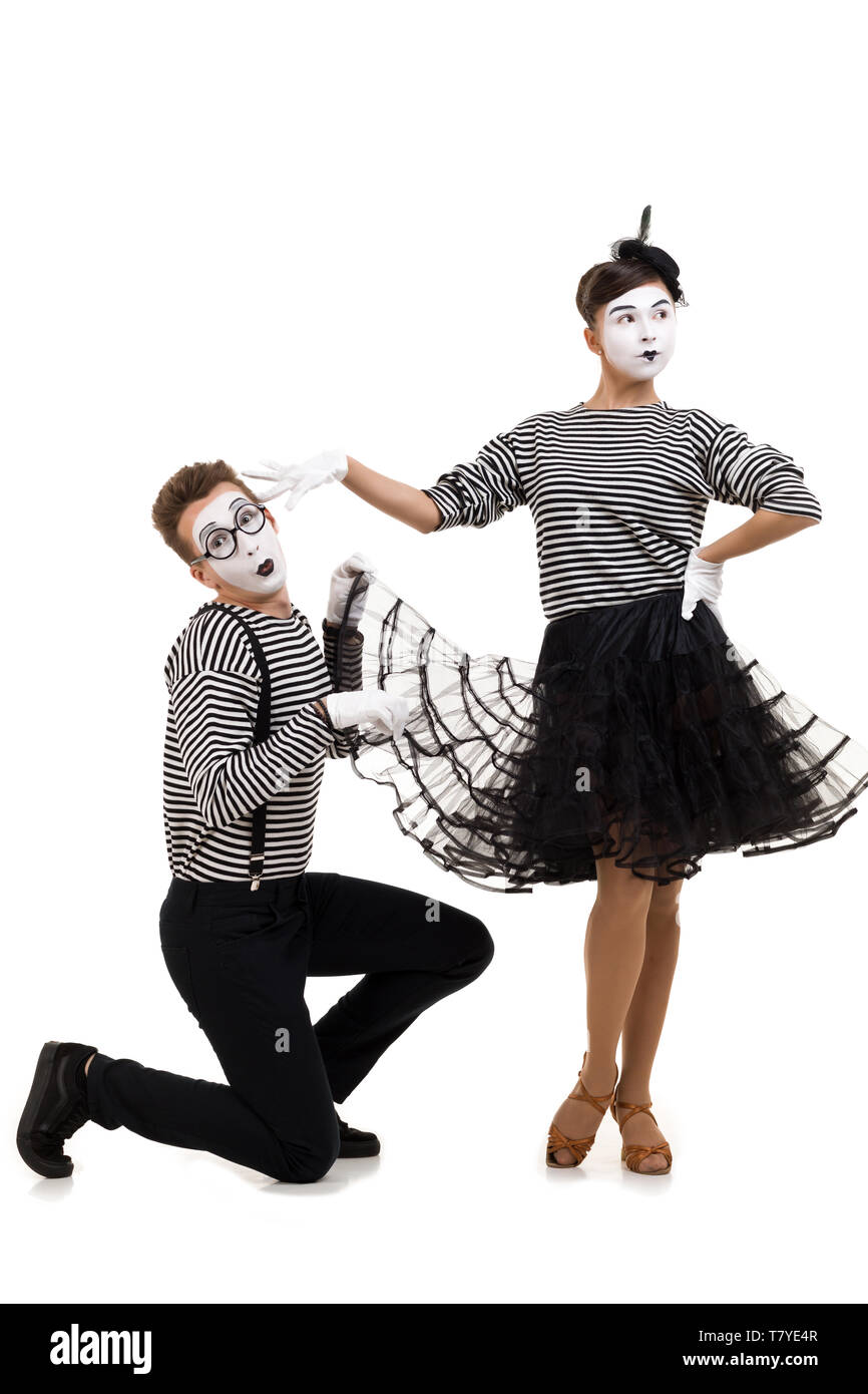 Smiling mimes in striped shirts. woman offended and man asks for forgiveness isolated on white background - Stock Image