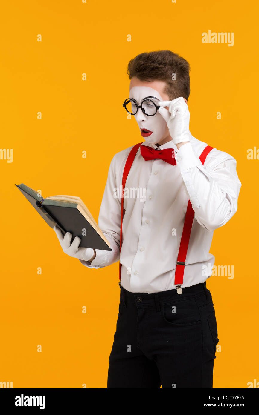 portrait of mime man artist reading book isolated on yellow background - Stock Image