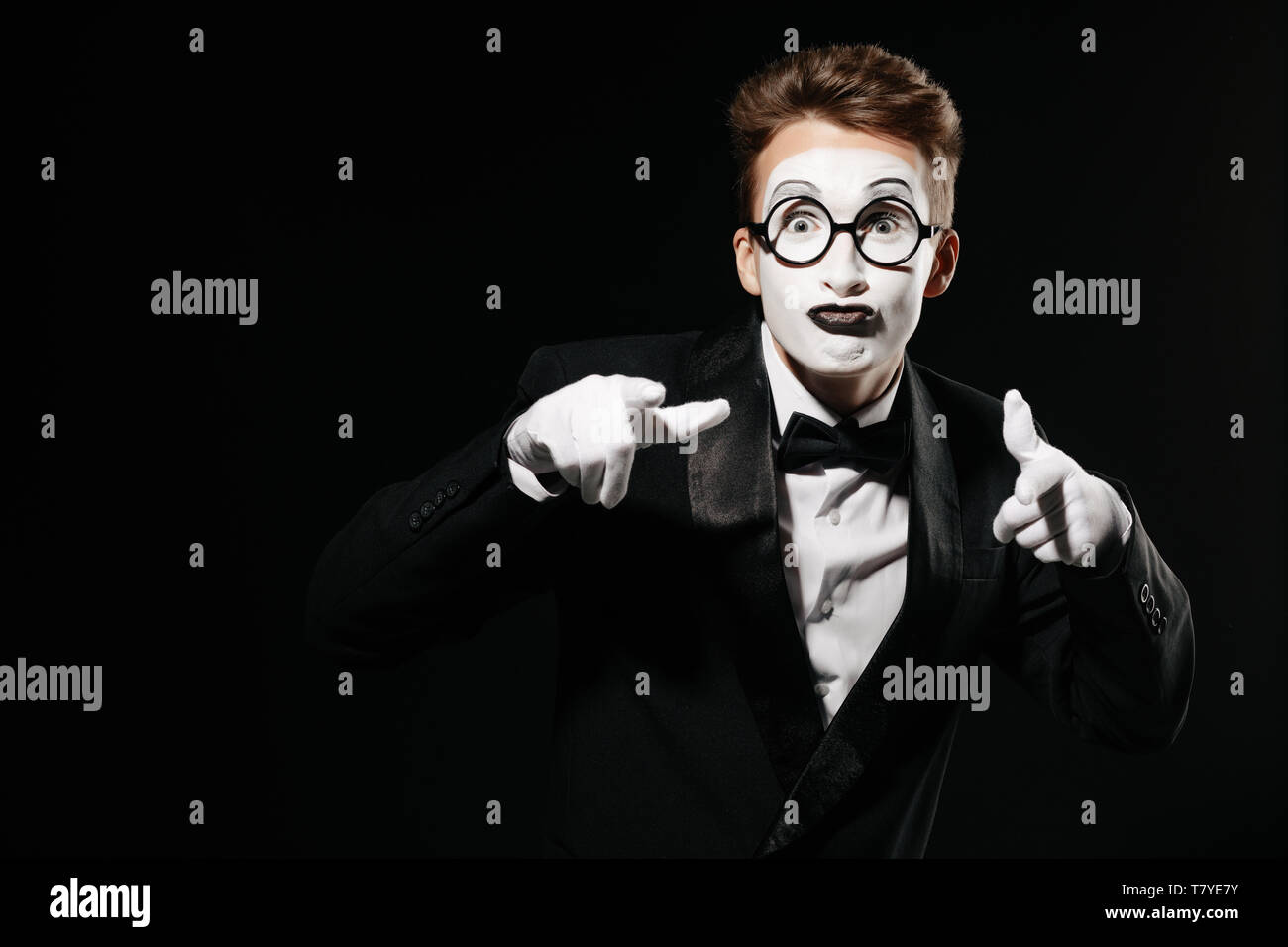 portrait of mime man in tuxedo and glasses points at you on black background - Stock Image