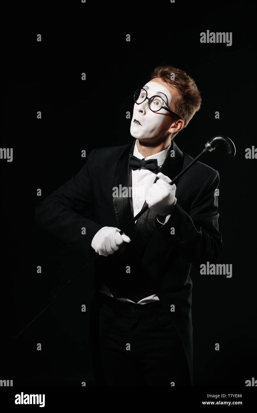 portrait of mime man in tuxedo and glasses posing with walking stick on black background - Stock Image