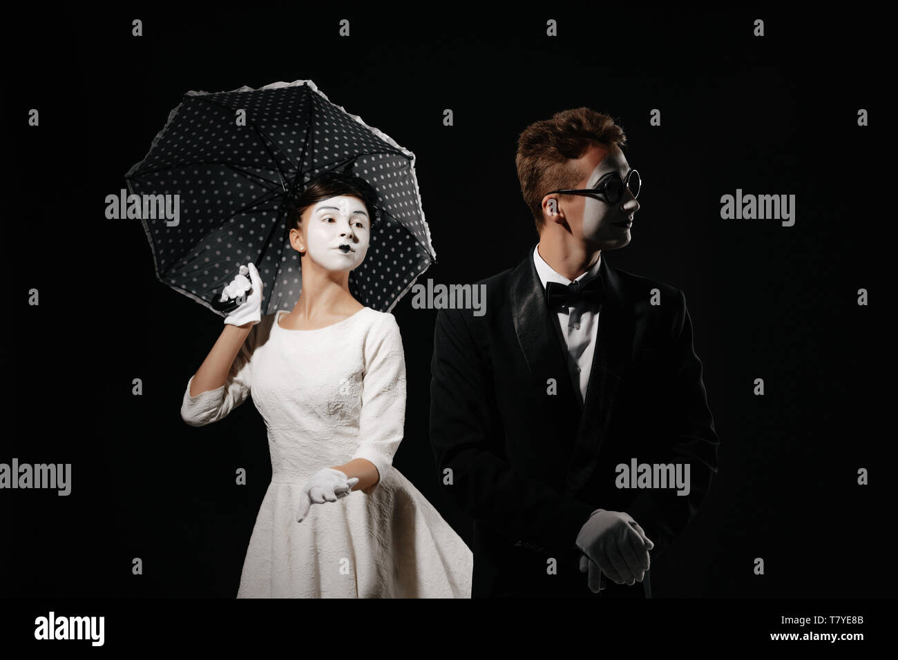 portrait of couple mime with umbrella on black background. man in tuxedo and glasses and woman in white dress. relationship - Stock Image
