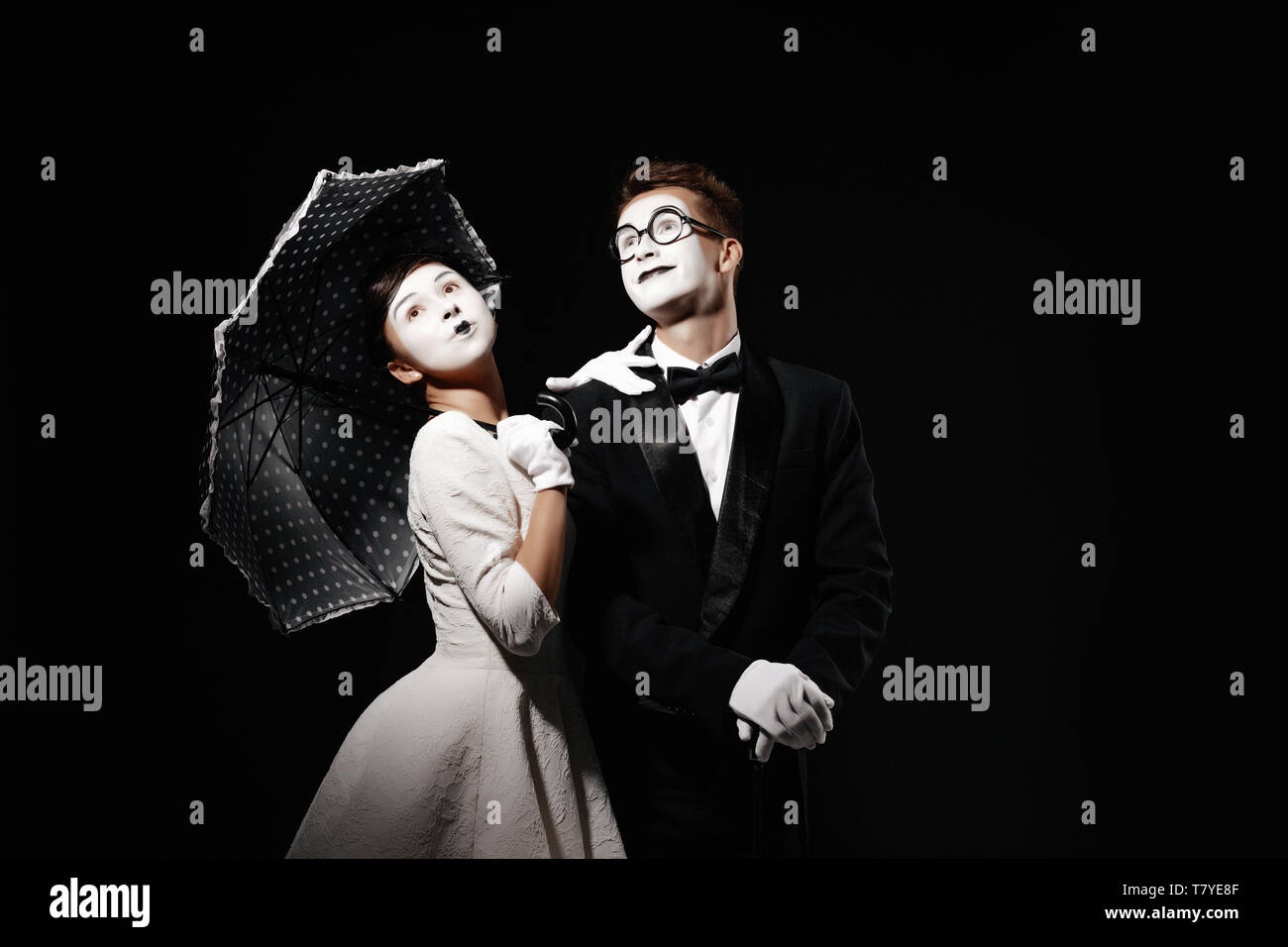 portrait of couple mime with umbrella on black background. man in tuxedo and glasses and woman in white dress. space for text - Stock Image