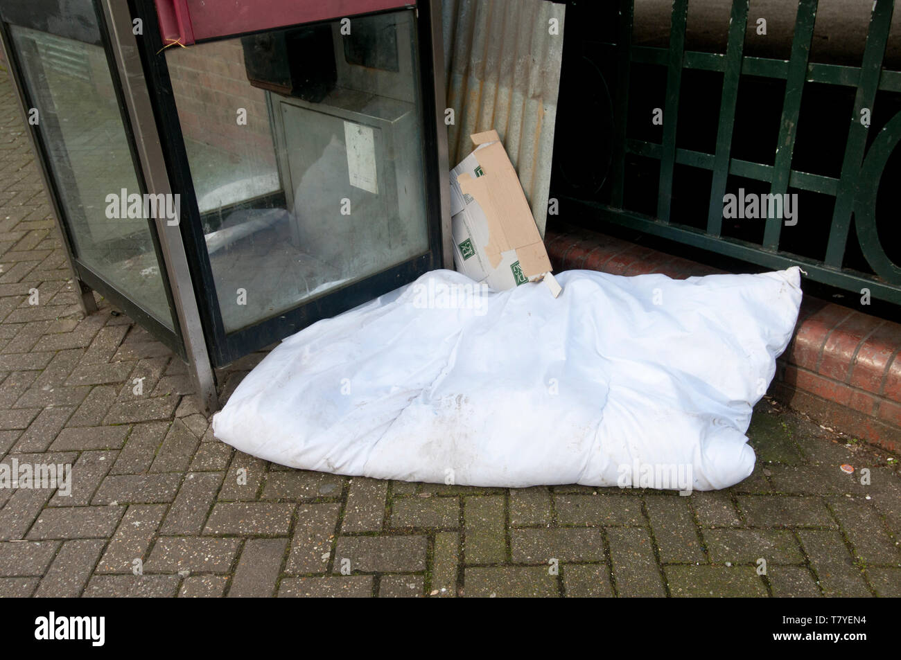 London, Hackney. Duvet bandoned by a rough sleeper, next to a phonebox. - Stock Image