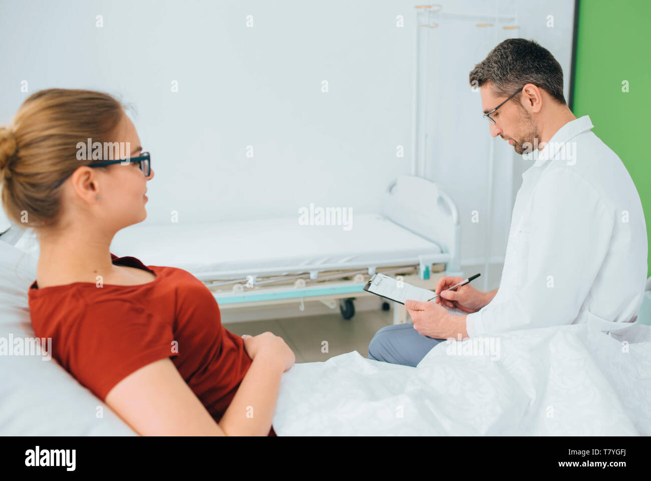 Doctor consulting patient in hospital room and through some notes - Stock Image