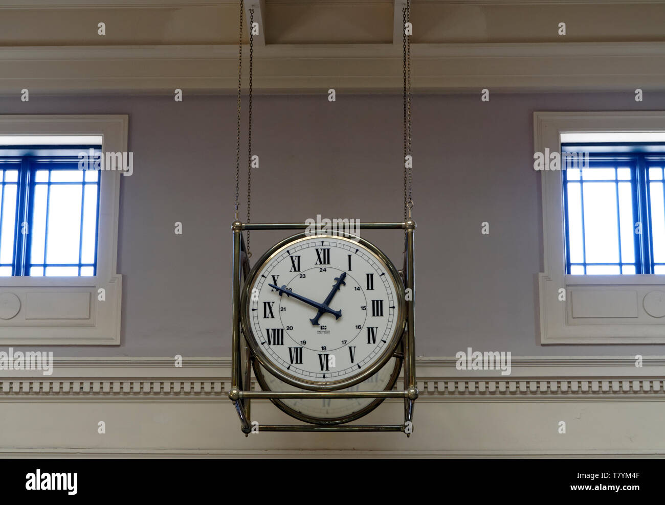 Suspended analog clock with Roman numerals in the Pacific Central train and bus station, Vancouver, BC, Canada - Stock Image