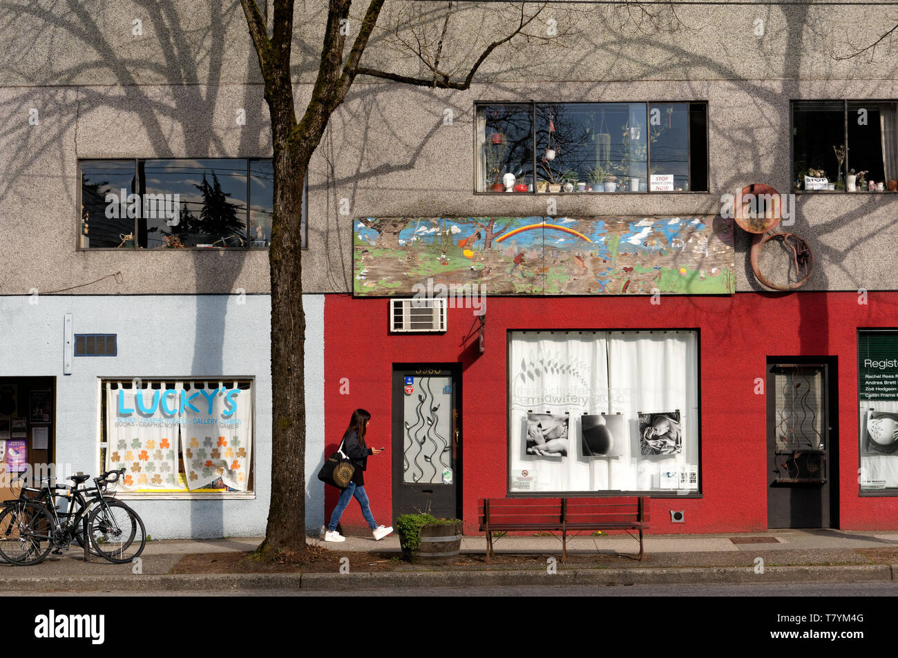 A young woman walking past colorful storefronts on Main Street, Vancouver, BC, Canada - Stock Image