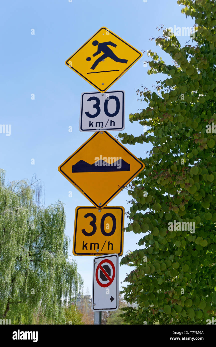 Multiple traffic signs and pictograms on a pole, Vancouver, BC, Canada - Stock Image