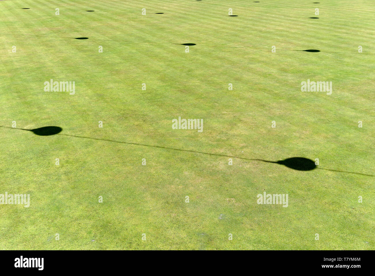 Shadows on a green lawn cast by overhanging electric lights forming a mathematical pattern - Stock Image