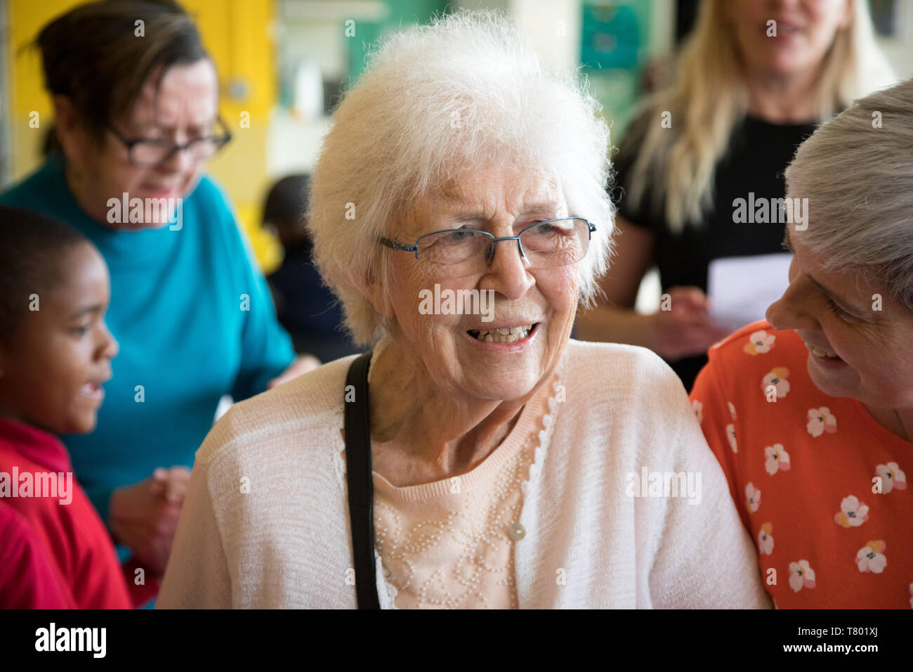 Elderly woman in a care home looking happy and positive, standing next to a carer on her left, with a school boy in background. - Stock Image