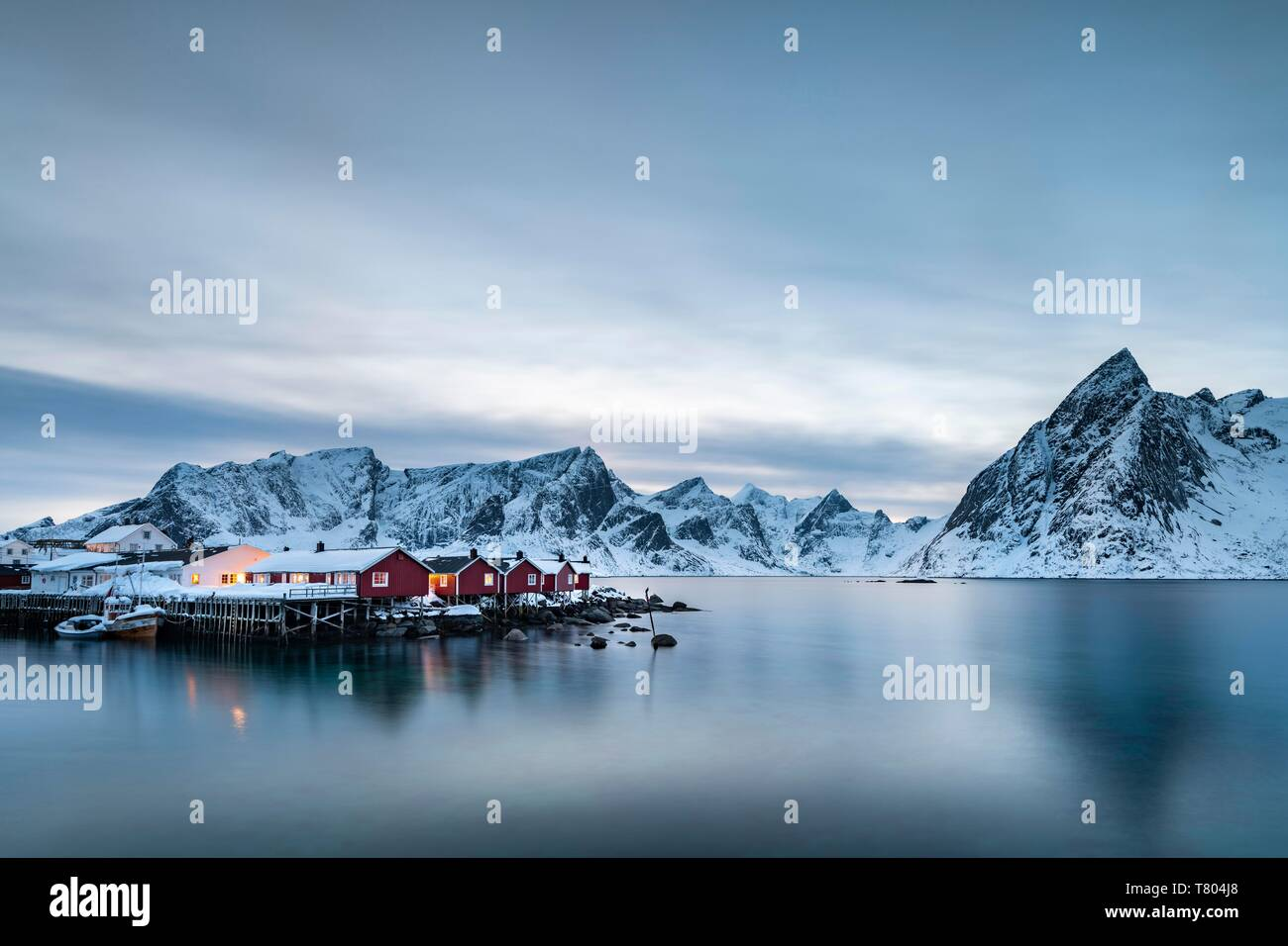 Rorbuer huts of Hamnoy at the blue hour, behind snow-covered mountains, Olstinden, Hamnoy, Moskenesoya, Lofoten, Norway - Stock Image