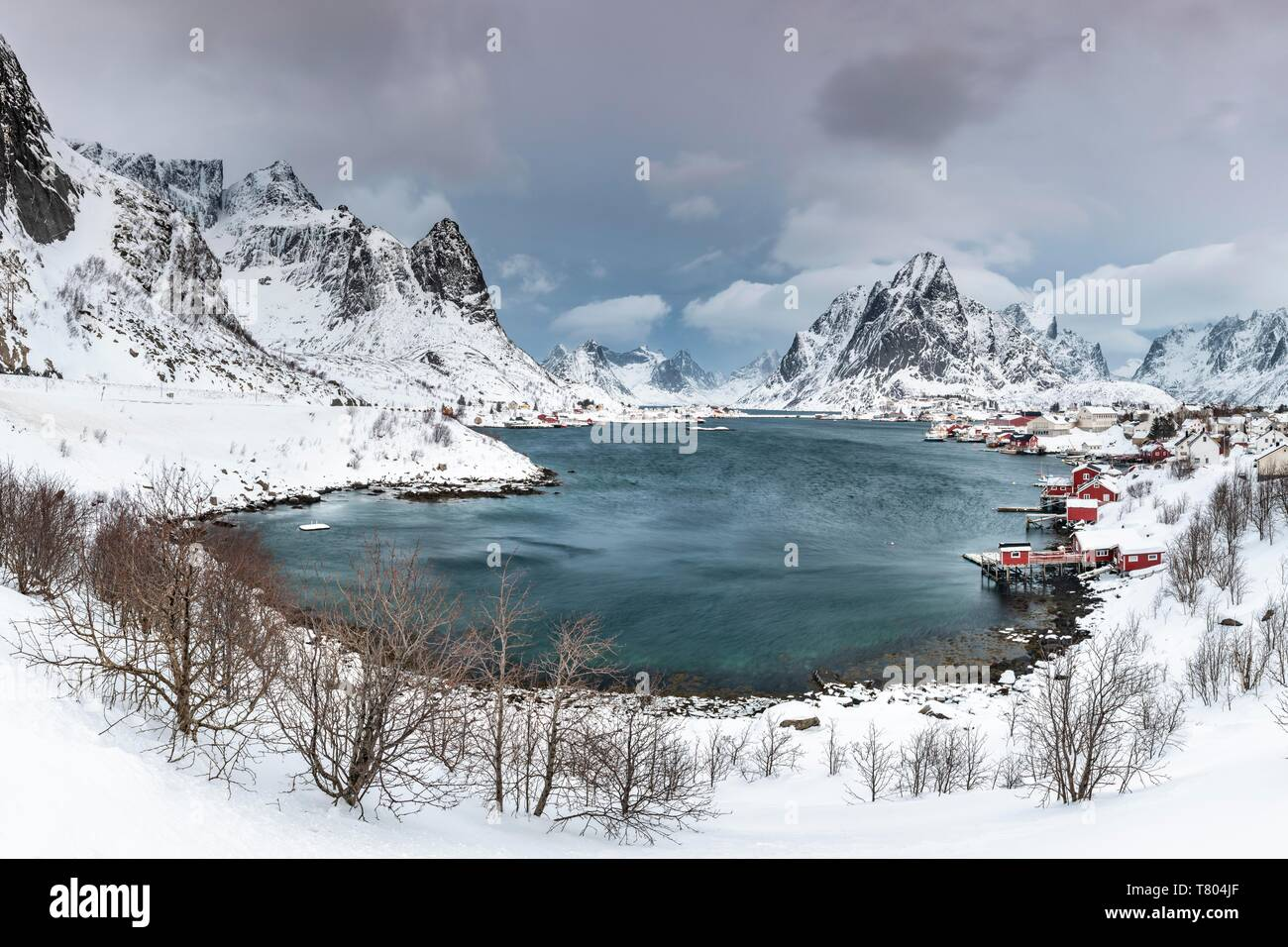 View of Reine with Reinefjord, snow-covered mountains at the back, Olstinden, Moskenesoya, Lofoten, Norway - Stock Image