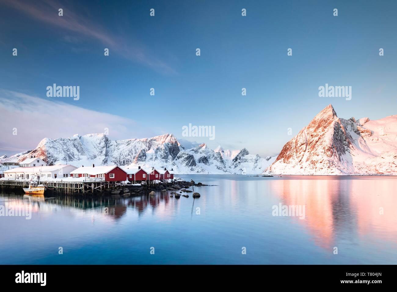 Rorbuer huts of Hamnoy at sunrise, behind snow-covered mountains, Olstinden, Hamnoy, Moskenesoya, Lofoten, Norway - Stock Image