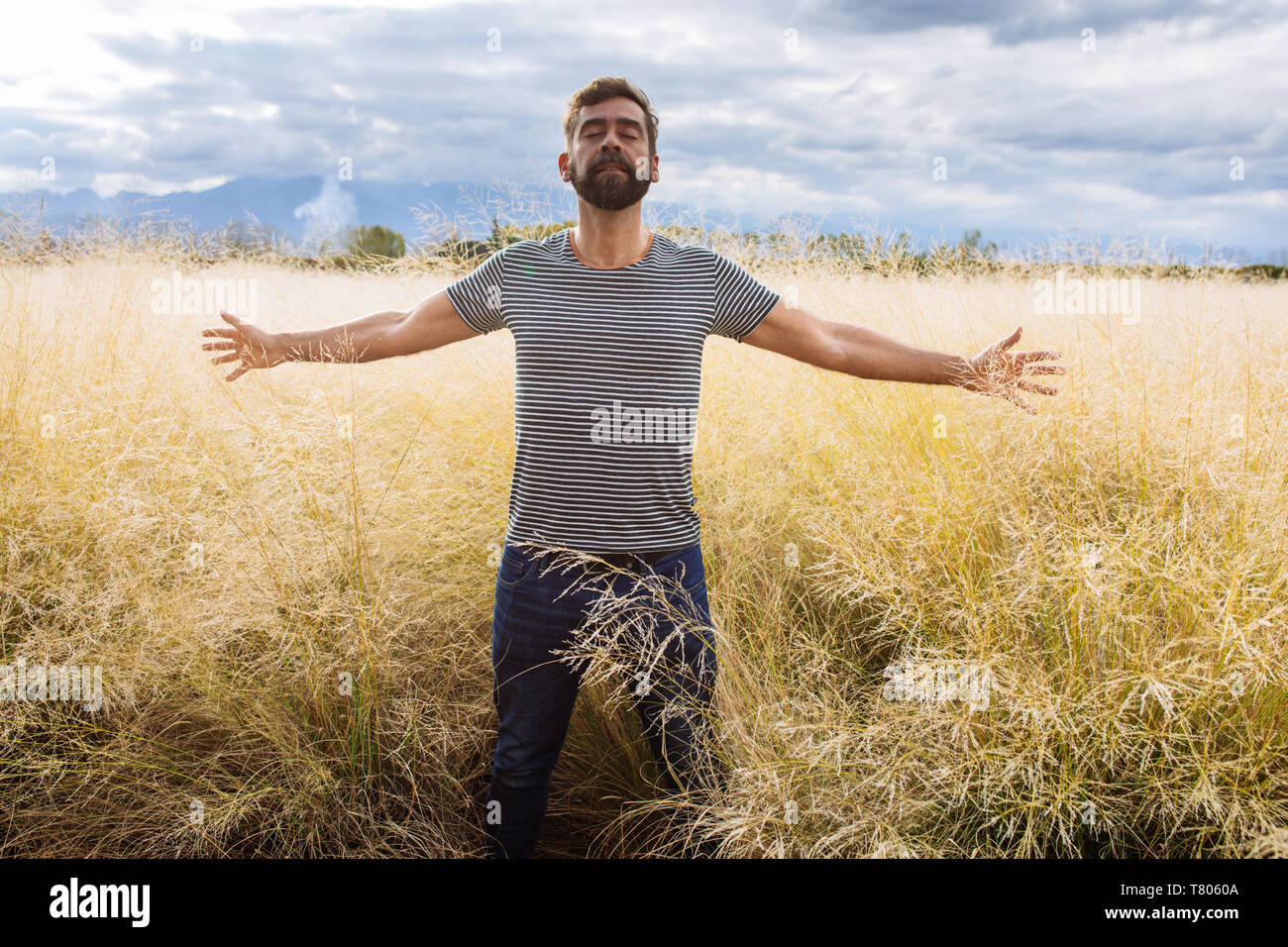 Man in his late thirties mid-fourties, posing with open arms and eyes closed in a yellow grass field in Bodega Septima Winery in Mendoza, Argentina Stock Photo