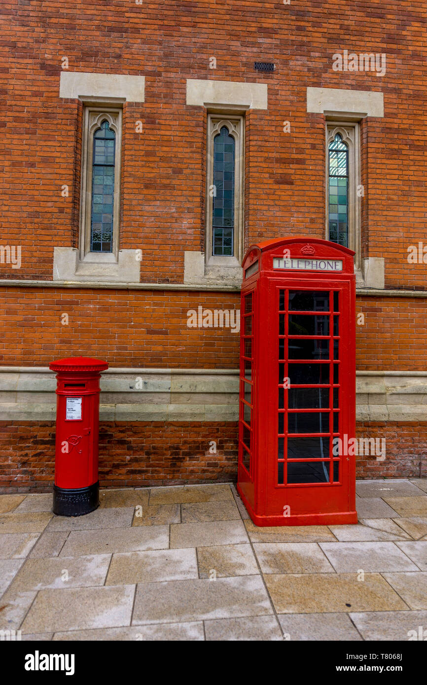 red telephone kiosk and red post box next to each other in front of a brick building. - Stock Image