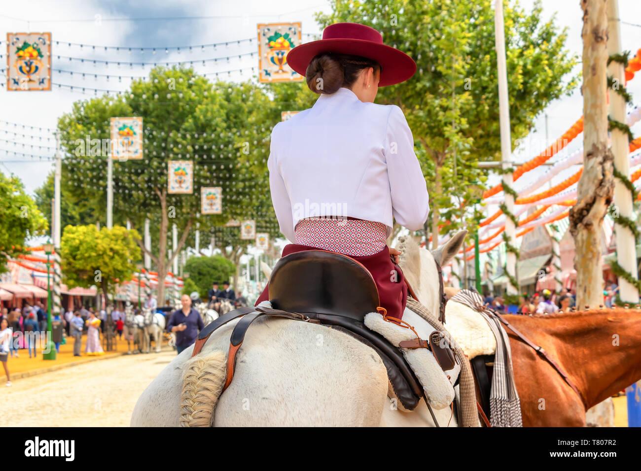 Beautiful Women riding horses and celebrating Seville's April Fair, Seville Fair (Feria de Sevilla). The Seville April Fair on May, 5, 2019 in Seville - Stock Image