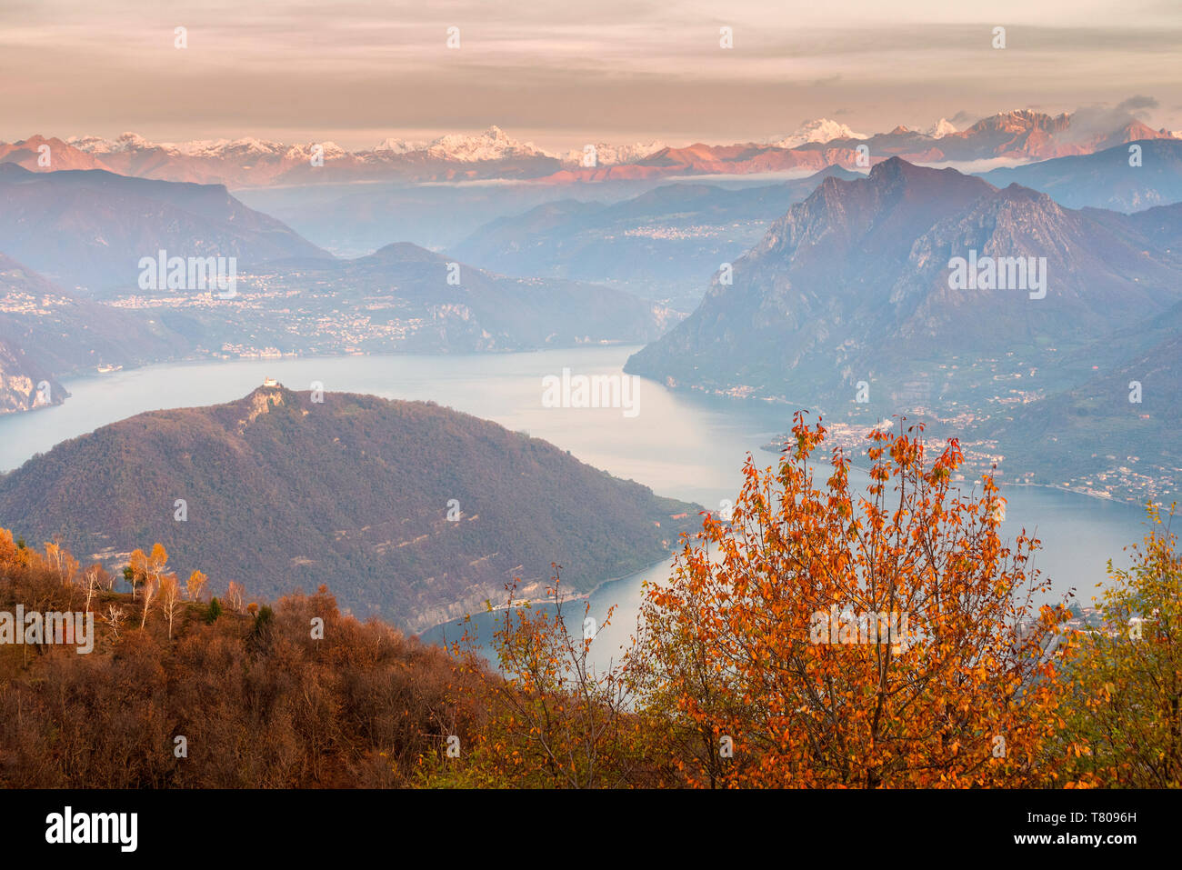 Iseo Lake, Monte Isola and Orobie Alps at sunset with fog in autumn season, Brescia Province, Lombardy, Italy, Europe - Stock Image