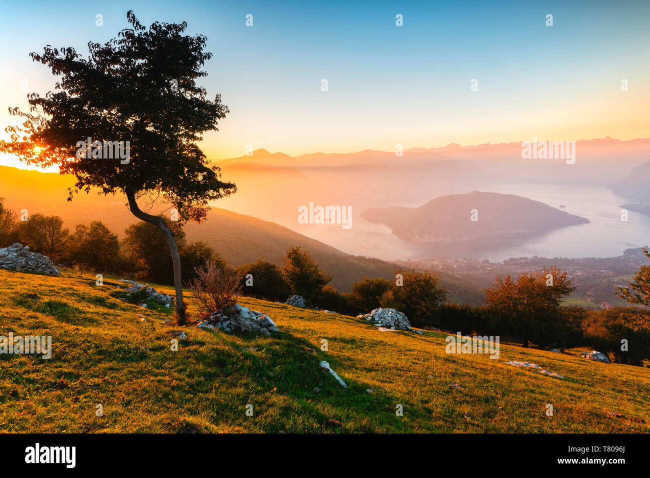 Iseo Lake and Monte Isola at sunset with fog in autumn season, Brescia Province, Lombardy, Italy, Europe - Stock Image