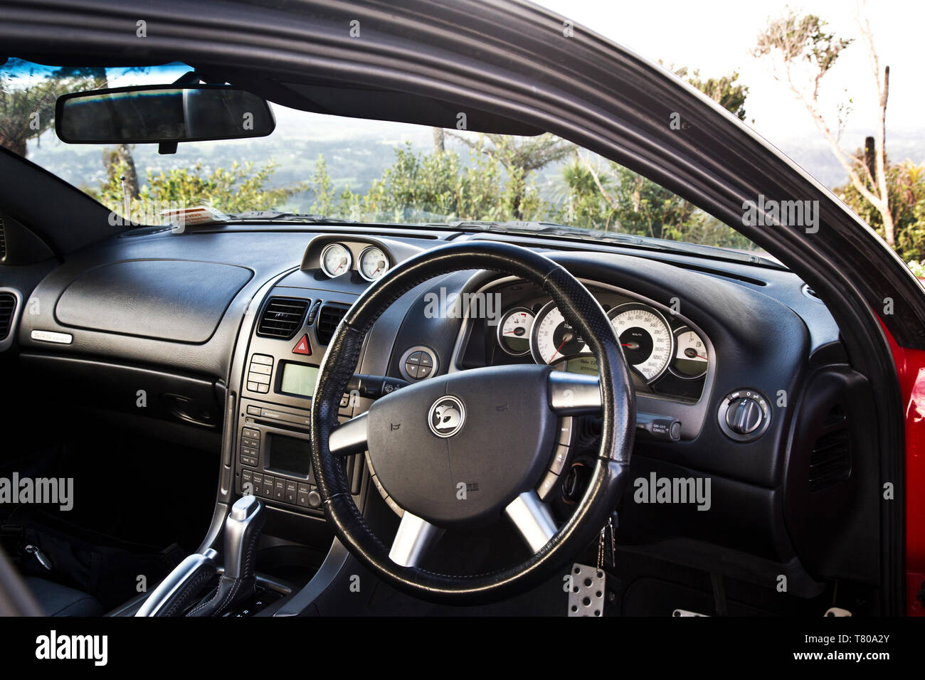 Red Holden Monaro HSV Coupe II 2003 GTO, Vauxhall, Pontiac GTO, Chevrolet Lumina Coupé. Showing the dashboard and front interior with bush. - Stock Image
