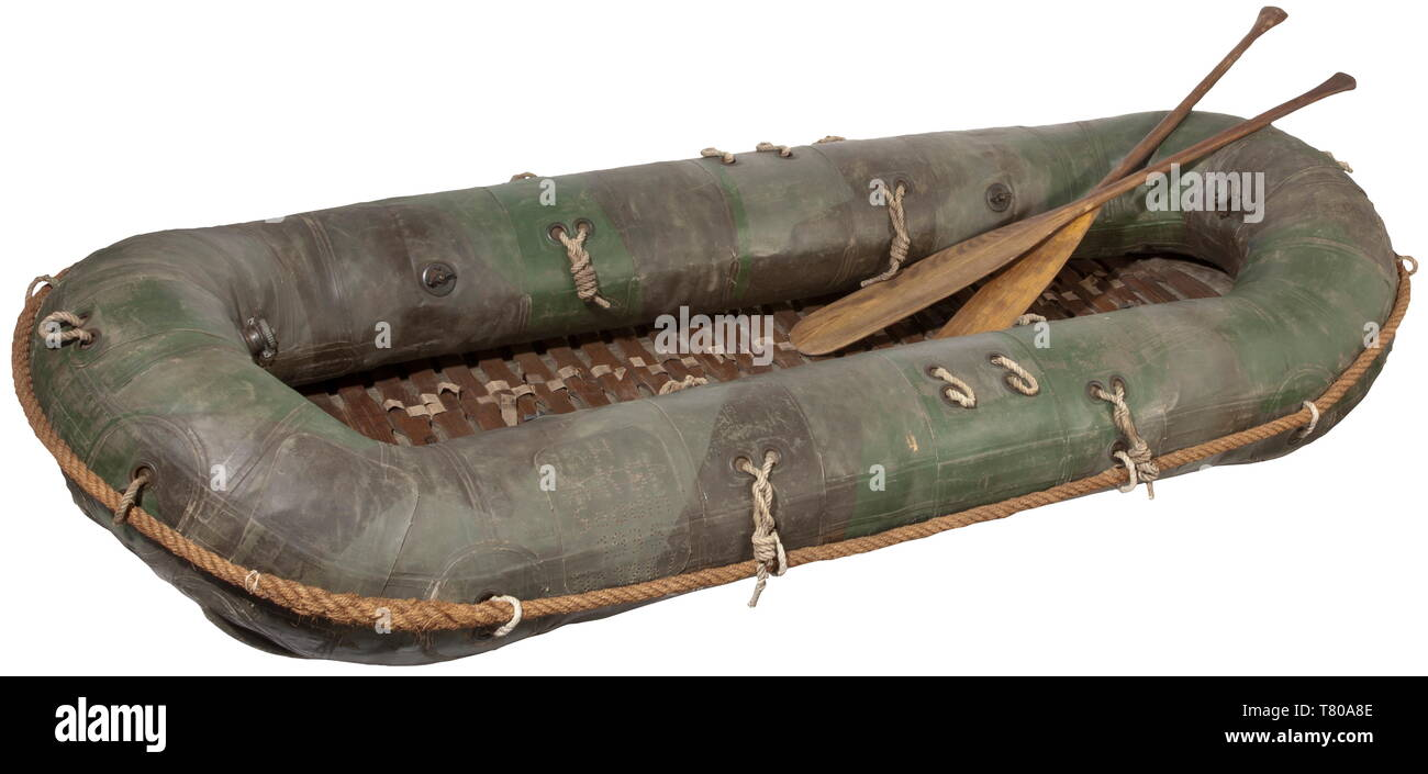 A rubber raft for pioneers - type Floßsack 34 Made of multi-coloured dark green to black heavy rubber material. Multi-compartment system with several admission valves. A fish symbol as well as maker designation 'H-KSI-Seddin', year of manufacture 1935 and number '1267'. Numerous loops and a continuous hand rope, removable wooden deck. Not checked for functionality. Dimensions ca. 120 x 300 cm, with two wooden paddles and a foot pump. Of German production, made in Seddin near Potsdam. Load capacity eight persons, specially developed for amphibious operations of the Wehrmacht, Editorial-Use-Only - Stock Image