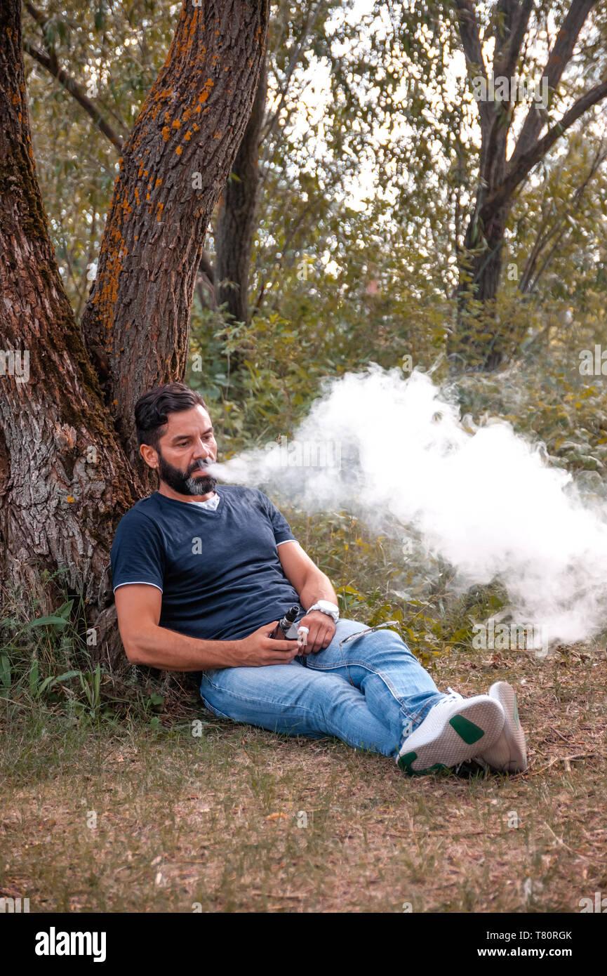 Modern vaper enjoying an e-cigarette. Getting rid of nicotine addiction. - Stock Image