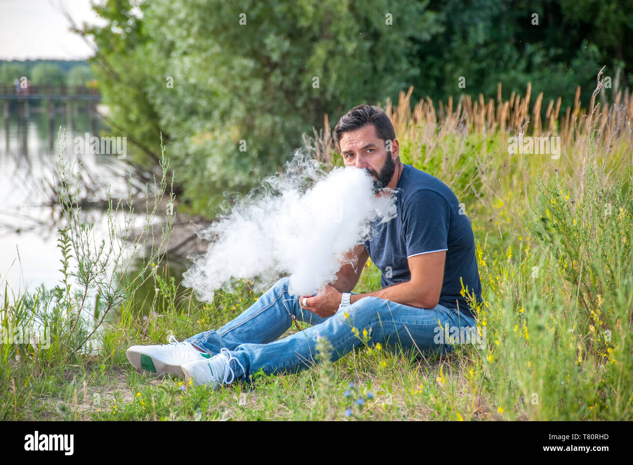 Stylish brutal smoker smoking an electronic cigarette in the daylight. Non-tobacco smoking. - Stock Image