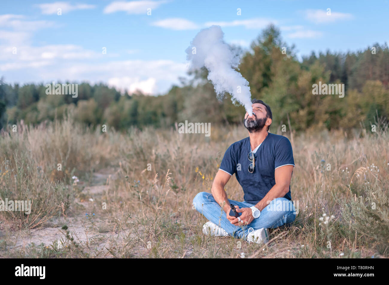 Brutal vape man hold and smoking his electronic smoke device blowing a stream of smoke spread. Stylish man. - Stock Image