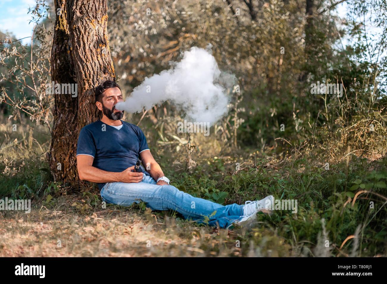 Handsome smoker enjoying an e-cigarette. Electronic cigarette. - Stock Image