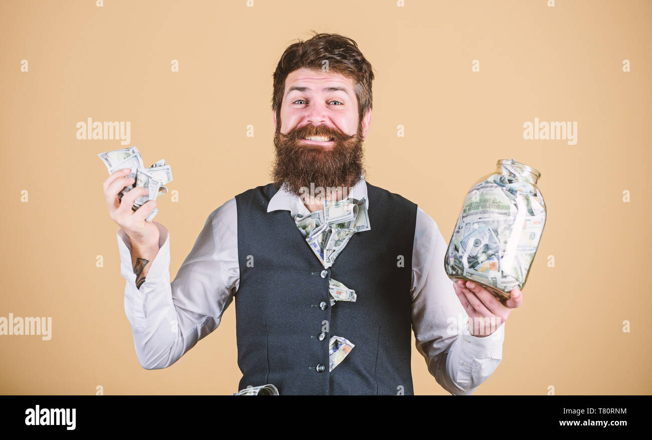 Safe place to keep money. Personal accountant. Businessman with his dollar savings. Richness and wellbeing. Security and money savings. Banking concept. Man bearded guy hold jar full of cash savings. - Stock Image